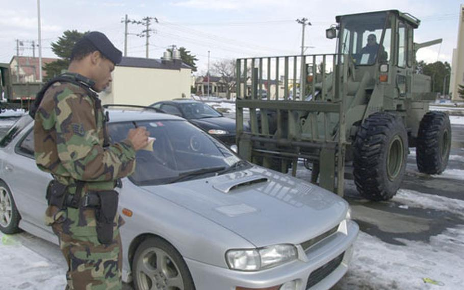 Staff Sgt. Eric Horace, a cop with the 35th Security Forces Squadron at Misawa Air Base, Japan, writes up a ticket for a vehicle left in a parking lot scheduled for snow removal Tuesday.