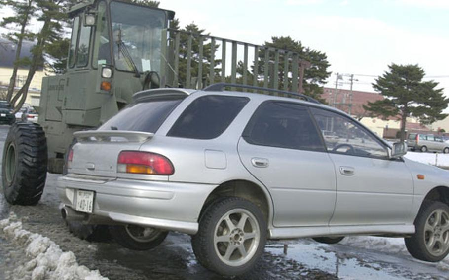 A car is fork-lifted from a dormitory parking lot at Misawa Air Base, Japan, so plows can clear snow. Vehicles not removed during designated plow times are towed across base.