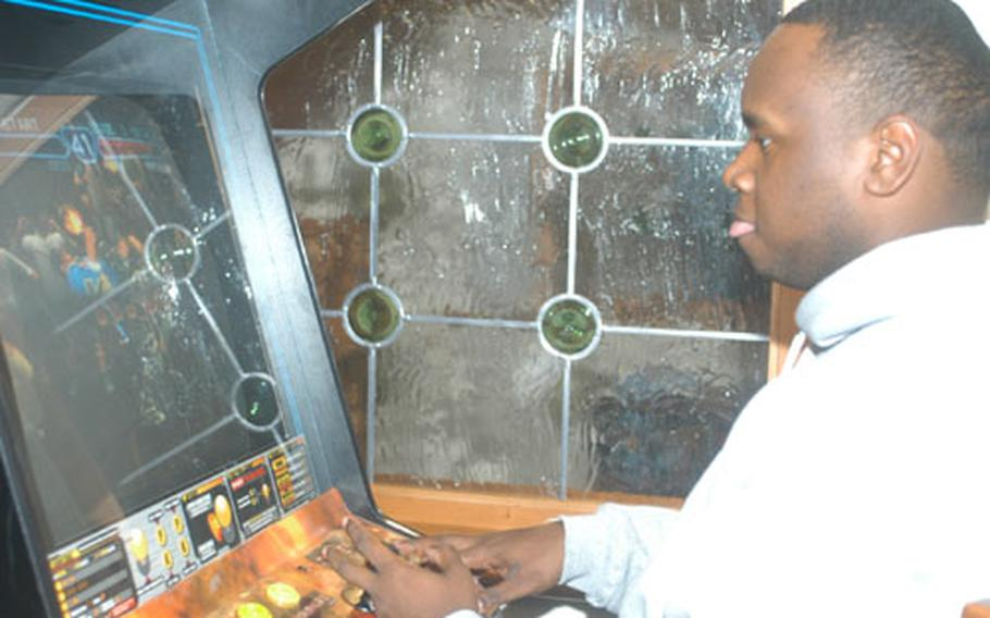 Sgt. Jaleel Sadiq, a supply sergeant with Headquarters and Headquarters Company, 1st Armored Division, on R&R leave in Garmisch, Germany, after eight months in Iraq, plays Street Fighter, while taking a break from skiing and sightseeing.