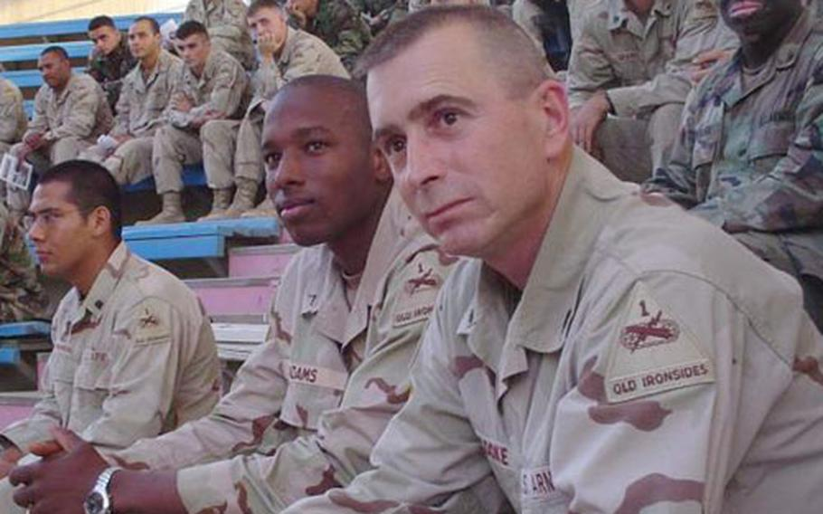Command Sgt. Maj. Eric Cooke, foreground, of the 1st Armored Division's 1st Brigade, watches an event with soldiers in Iraq. Cooke was killed on Christmas Eve in Baghdad.