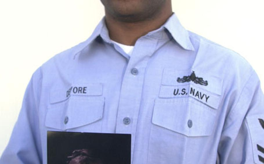 Petty Officer 2nd Class Kemo Devore, who works in the Port Operations department at Naval Station Rota, Spain, holds a photo of his sister, Kimberly Devore. He donated a kidney in August to his sister in the United States. Both have recovered from the surgery and are doing well.