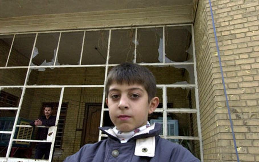 An Iraqi boy stands on the gate outside his house. The concussion for the car bomb blew out the windows of shops and houses for blocks.
