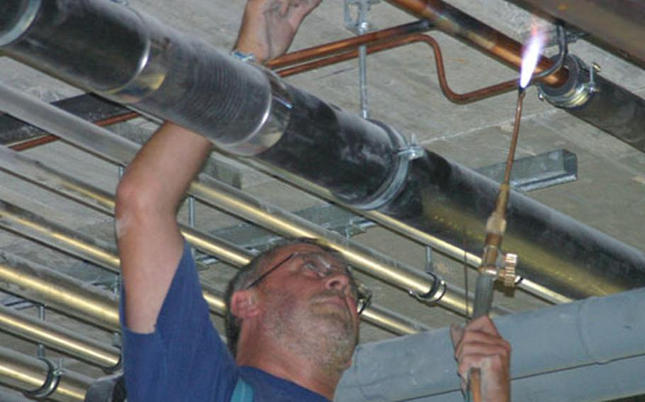 A worker solders pipes at the Edelweiss Lodge and Resort being built in Garmisch, Germany.