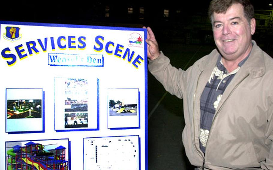 Bob Smith, community support flight chief for Misawa Air Base's 35th Services Squadron, stands next to a poster board of photos showing the different recreational sections planned for the Weasel's Den.