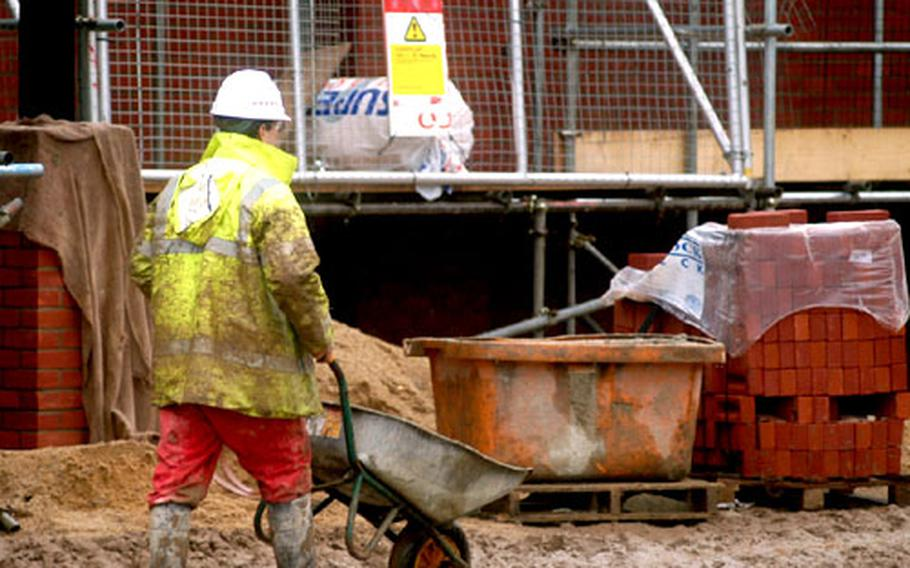 A worker makes his way across a soggy construction site Tuesday at RAF Mildenhall, England. Work at the community development site will eventually mean a new home for such community functions as the post office, bowling center and community center.
