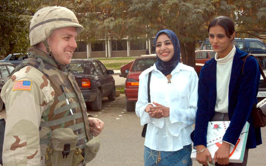 Pfc. Justin Bellatti, 25, of Wichita, Kan., chats with two Baghdad University students, Evaan and Juana, last week on campus.