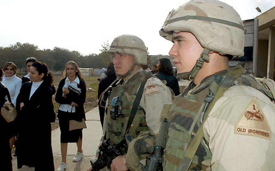 Spc. Nathan Reynolds, 21, of Las Vegas and Spc. Tristan Byers, 23, of New Brighton, Pa., watch a group of students passing by at Baghdad University in Iraq. Soldiers from Company A, 1st Battalion, 6th Infantry Regiment, who pull security at the campus are ordered not to fraternize with female students.