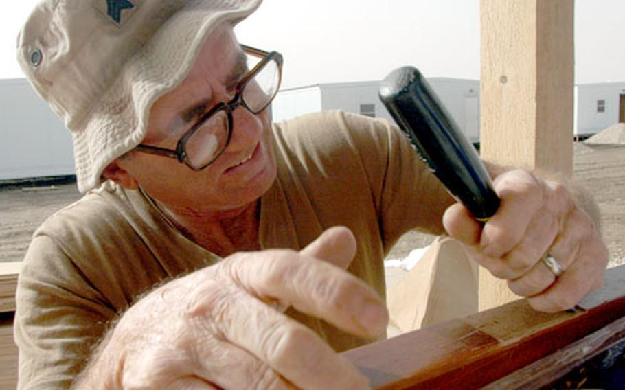 Using only a chisel, Sgt, Bruce Hofman, 58, of Webb City, Mo., gouges out a place to hang a door hinge.
