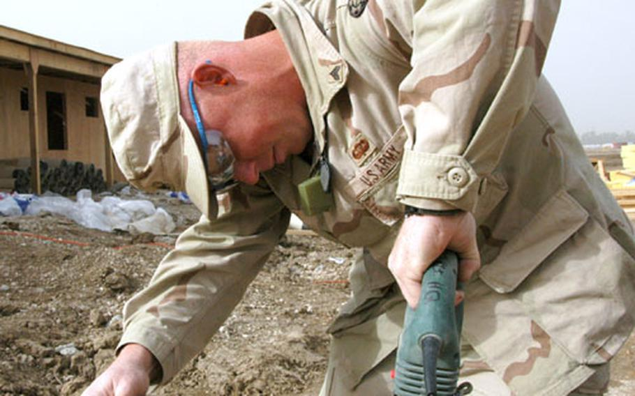 Sgt. Mike Doty, 28, of Springfield, Mo., cuts wood for a new building at Camp Victory-North in Baghdad.