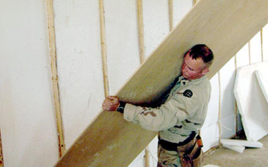 Sgt. Trent Gregory, 24, of Clinton, Mo., heaves a plywood sheet into place.
