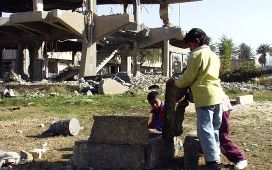 Iraqi children use the rubble to build things outside a bombed Baath party headquarters.