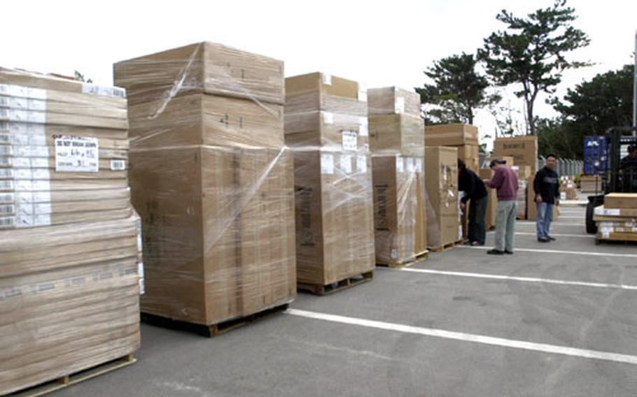 Okinawa District school supply personnel organize two truckloads of supplies received for the first-, second-, and third-grade classes on Okinawa.