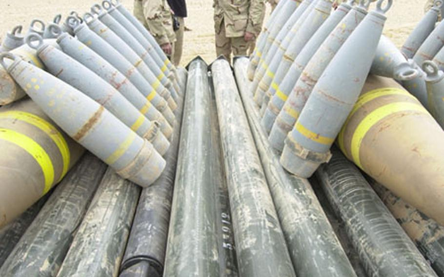 Soldiers look over the pile of Iraqi artillery shells, bombs and missiles being set up for demolition.