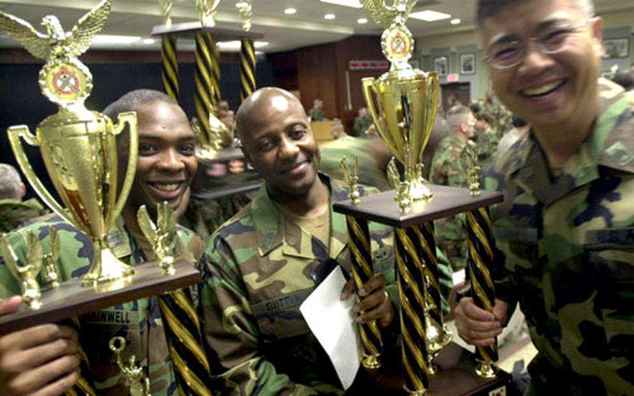 Capt. Anterrio Gainwell, left, Master Sgt. Jerome Sutton, center, and Staff Sgt. Daniel Soh from the 34th Support Group Motor Pool hoist their trophies for maintenance awards Tuesday.