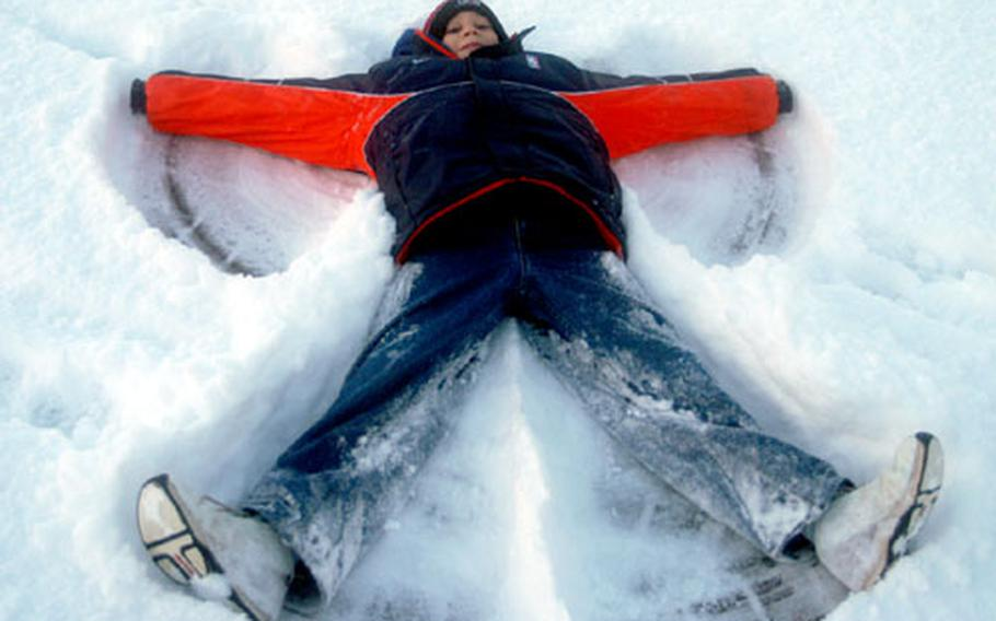 Caleb Spencer, 10, makes a snow angel Wednesday morning at RAF Mildenhall, England. A snowstorm closed Lakenheath Elementary School, where Caleb is a fourth-grader, along with other schools at RAF Lakenheath and RAF Feltwell.