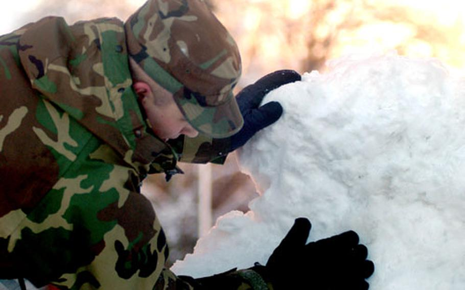 Airman 1st Class Adam Baldwin of the 100th Comptrollers Squadron at RAF Mildenhall, England, tries to fashion a dollar sign from a pile of snow at the base. Schools were closed and work was delayed after a snowstorm hit the area before midnight Tuesday.