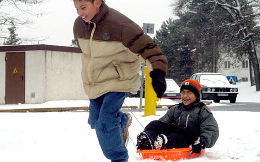 Brian Sullivan, 11, pulls Alexander Feliciano, 10, on a plastic sled during school hours on Lincoln Village in Darmstadt, Germany. Schools in Darmstadt closed early because of safety concerns, according to Lt. Col. L.J. Strife, 233rd Base Support Battalion commander.