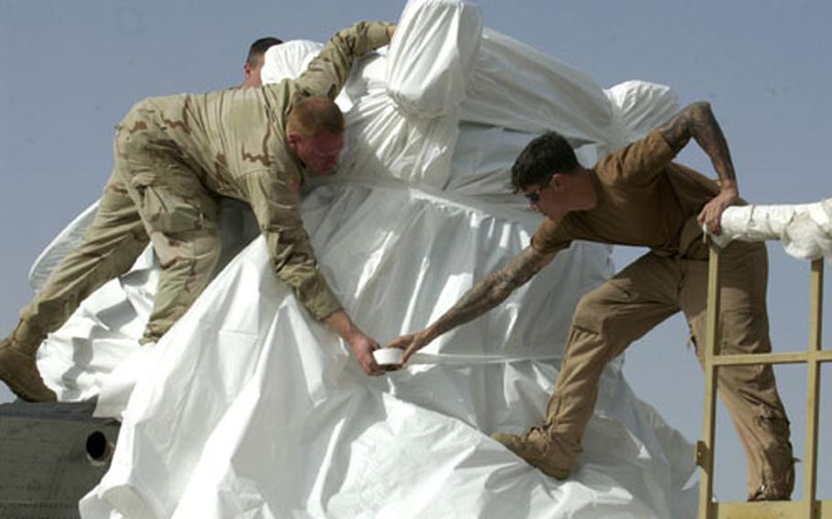 Soldiers from the Giebelstadt, Germany-based 159th Aviation Regiment, known as Big Windy, wrap plastic around a Chinook helicopter in preparation for their return to Germany.