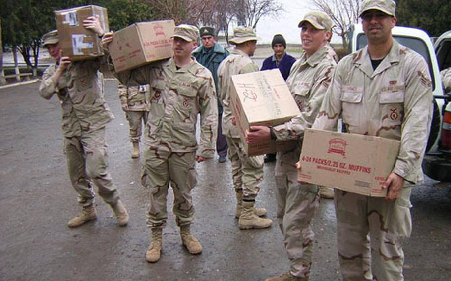 U.S. Air Force members unload donated supplies at a school in Khanabad, Uzbekistan. Students at Aviano High School in Italy solicited donations of school supplies from community members in December. The donations were sent to the former Soviet republic in care of the members of the 31st Security Forces Squadron deployed there.