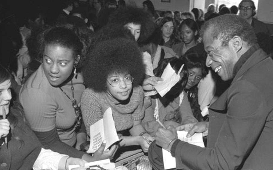James Baldwin participates in a panel discussion, then signs books for his admirers at Stuttgart, Germany, in February, 1973.