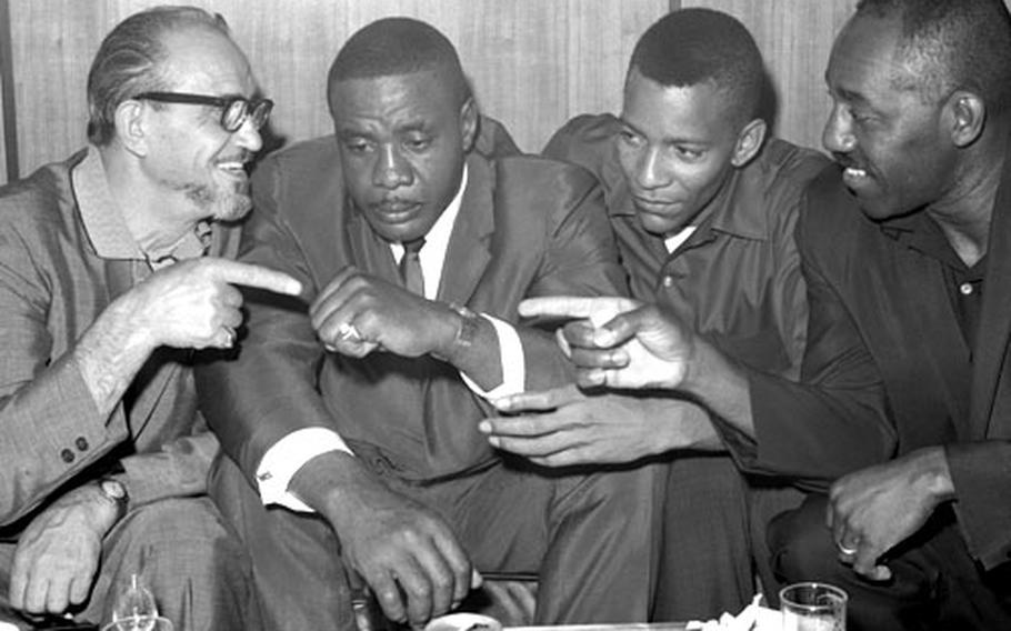 Sonny Liston, second from left, with trainer Joe Polino, left, sparring partner Jim Robinson, right, and assistant trainer Nate Richardson at the Frankfurt airport in August, 1966.