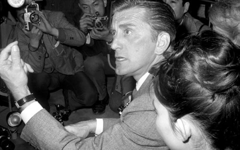 """Kirk Douglas and his wife, Anne, arrive in Tokyo in March, 1964. The actor was visiting Japan as part of a State Department program, as well as to promote his latest film, """"Seven Days in May."""""""