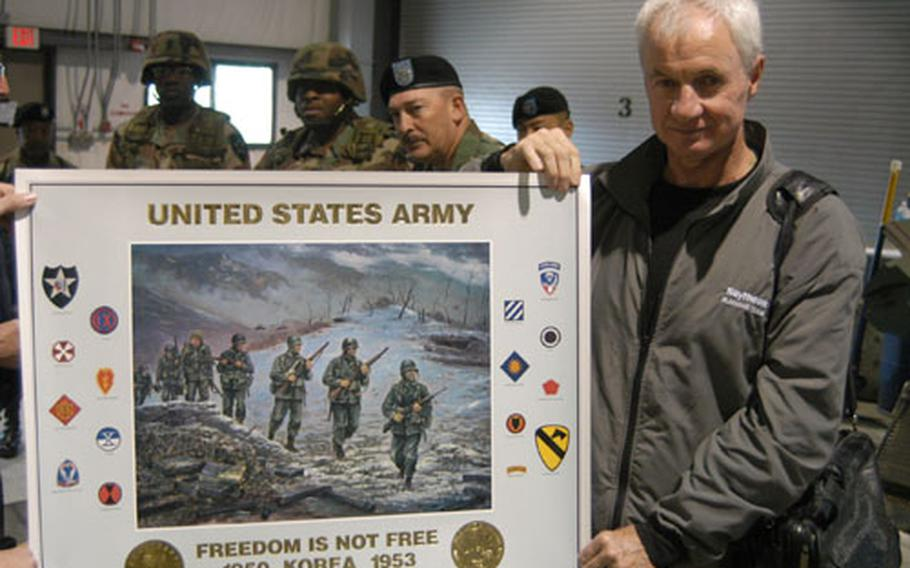 Association of the US Army artist Jim Ryan (right) displays a print he helped produce commemorating the Korean War while (from left) Command Sgt. Maj. James Daniels, Command Sgt. Maj. James Williams, and Command Sgt. Maj. James Lucero look on.