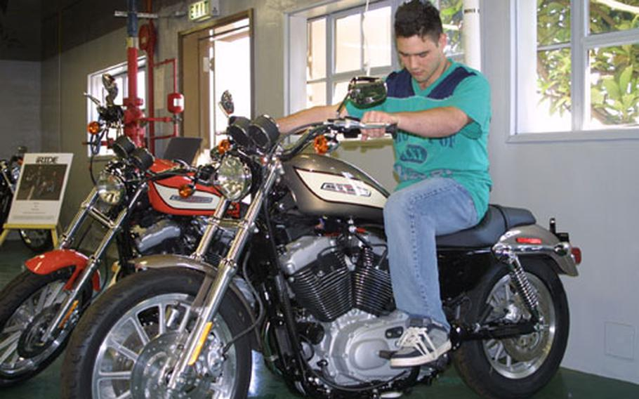 Navy Airman Matthew Guyette, of Helicopter Antisubmarine Squadron 14, checks out a motorcycle at the newly opened Harley Davidson showroom at Naval Air Facility, Atsugi. This and many other bikes are on display. The showroom's grand opening is scheduled for Saturday, with a ribbon-cutting ceremony at 10 a.m.