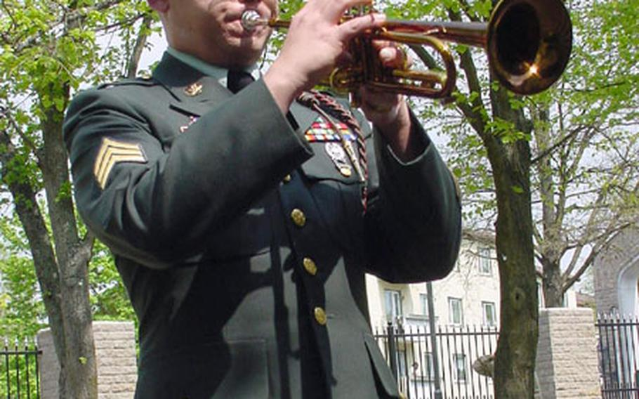 Sgt. Michael Daly, 1st Infantry Division Band, plays Taps to salute Pfc. Shawn Edwards, who was killed last week in Iraq.
