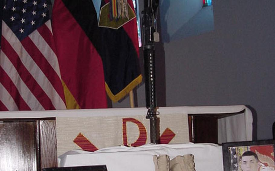 The traditional boots, rifle, helmet and photographs of Pfc. Shawn Edwards are displayed on a podium at Leighton Chapel in Würzburg.