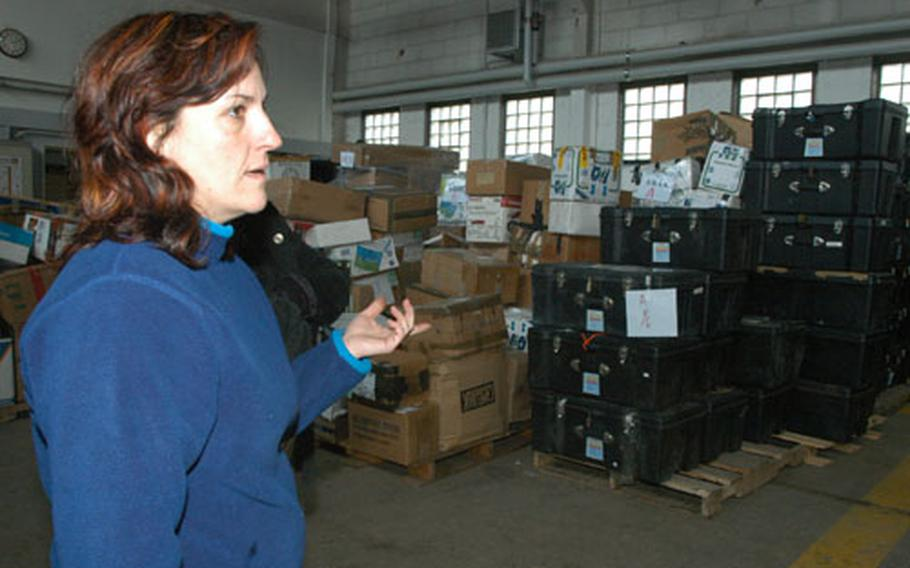 Idalia Leza, mail supervisor in Baumholder, Germany, points out the piles of boxes and footlockers that troops downrange sent home. Mail workers are storing it in two motorpool warehouses.