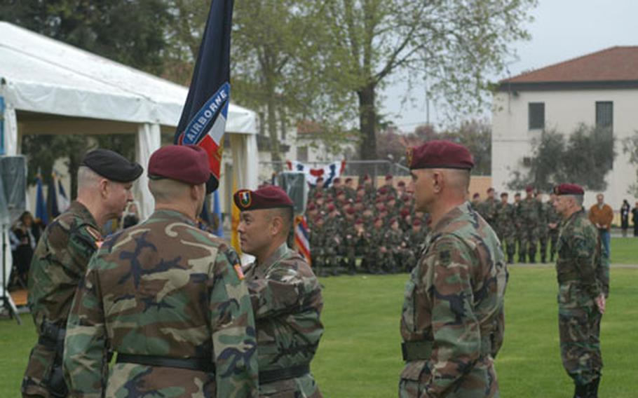Gen. B.B. Bell, U.S. Army Europe commander, hands the guidon to Brig. Gen. Jason K. Kamiya during a change-of-command ceremony Friday at Caserma Ederle in Vicenza, Italy. Maj. Gen. Thomas R. Turner, looking on, relinquished command of the Southern European Task Force (Airborne).