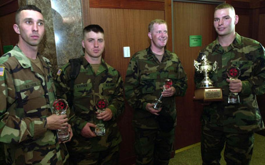 Spc. Jonathan Waldron, Pfc. Thomas Vander, Sgt. Gregory Bodin and Pfc. Andrew Mach-Miller, all of the 702nd Main Support Battalion at Camp Nimble, hold glass trophies Friday for placing first in a water purification competition held last week.