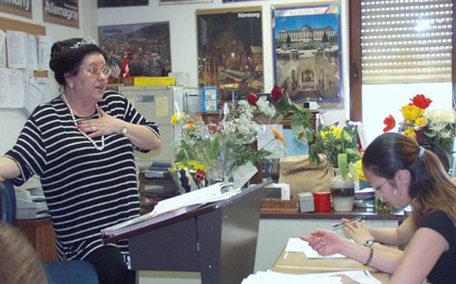 """Her desk teeming with flowers from children, Ursula Karsten teaches German to seventh- and eighth-graders at Würzburg Middle School, Germany. The school declared Friday """"Frau Karsten Tag"""" in honor of her 40 years as a Department of Defense Dependents Schools teacher of German language and culture."""