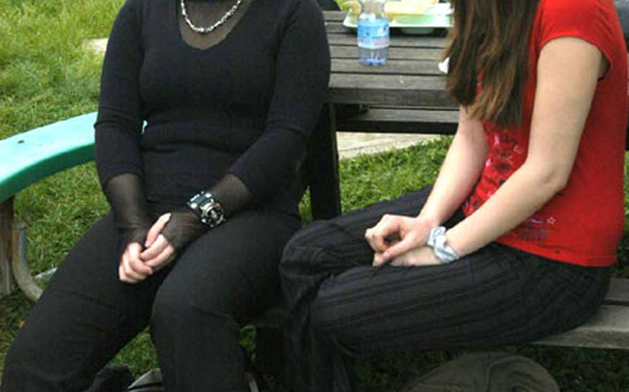 Tenth-graders LaDeanna Spraggins, left, and Amanda Harris sit outside during lunch at Naples American High School in Italy. LaDeanna said that while she understands why revealing clothes are banned, she disagrees with the ban on spiked clothing and doesn't understand why she was told to remove her watch, which has a skull on it.