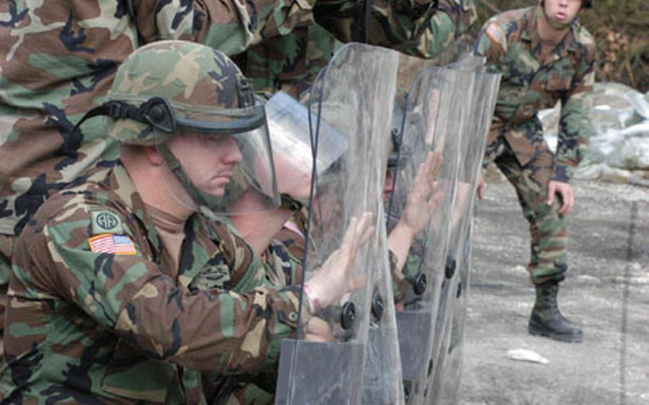 Staff Sgt. Cory Bourn instructs soldiers of Company A, 2nd Battalion, 152nd Infantry Regiment during a non-lethal weapons training at Eagle Base on Wednesday. During an eight-hour course, three companies of U.S. peacekeepers learned baton tactics, crowd control skills and how to use non-lethal ammunitions in case they needed to control a riot.