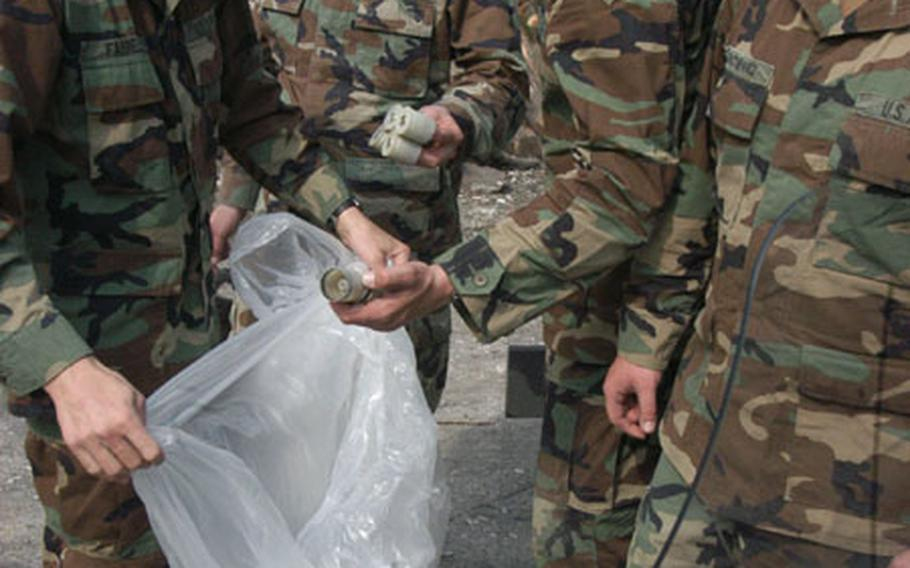 Soldiers collect casing for rubber pellets' casings to be refilled and reused in future non-lethal weapons training.