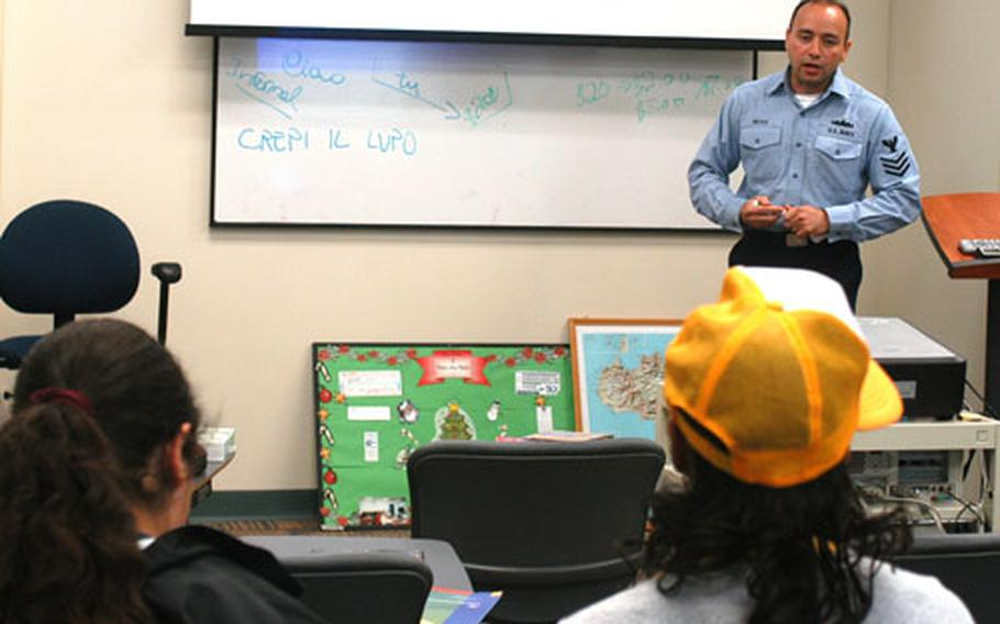 Petty Office 1st Class Walter Nieves, Naval Air Station Sigonella command financial educator, talks with children about money management in a Budgeting for Kids class in the base Fleet and Family Support Center.