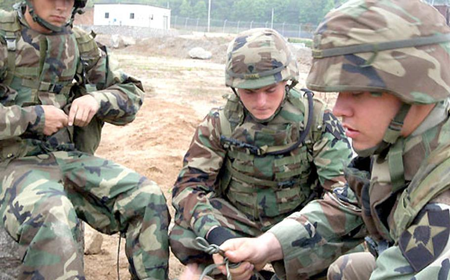 Spc. Jason Trudeau, Spc Price Neal, and Pfc. Daniel Sharon, left to right, of the 2nd Engineer Battalion tie det-cords at Warrior Valley.