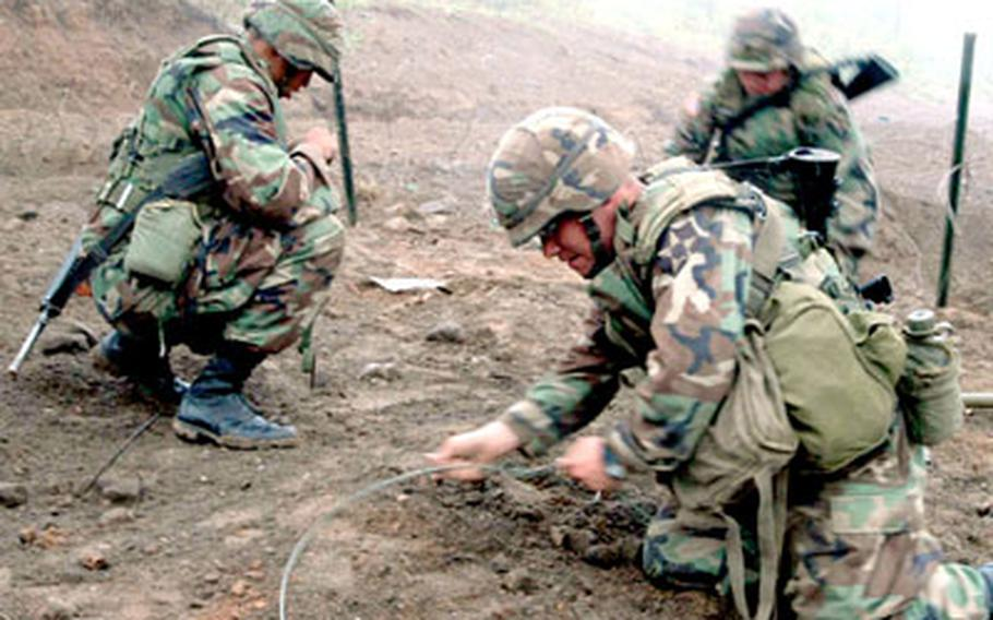 """Pfc. Jose Morales, foreground, Sgt. Juan Cabello, left, and Pvt. Jonathan Miller of 2nd ID's 2nd Engineer Battalion place C4 explosive to clear a """"minefield"""" at Warrior Valley on Monday."""