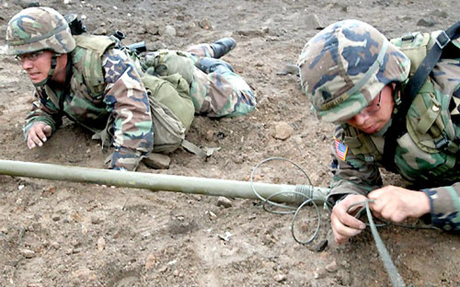 """Pfc. Jose Morales and Sgt. Juan Cabello place Bangalores to clear wire from a """"minefield"""" at Warrior Valley."""