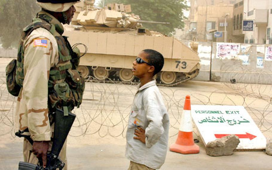 Spc. Kyron Regis and 10-year-old Sayf have a talk at the Palestine Hotel checkpoint.
