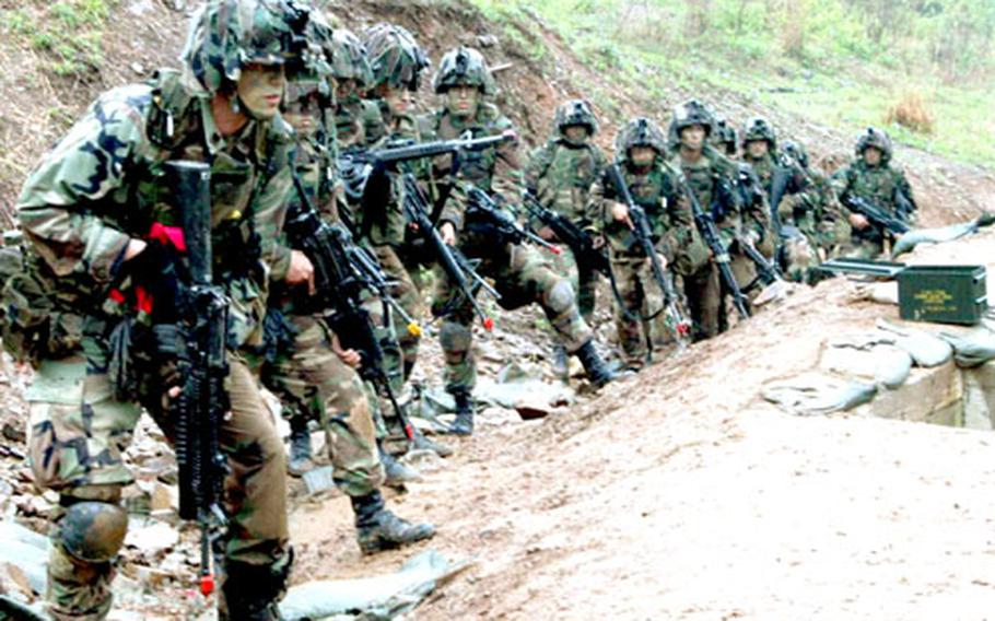 Soldiers from 2nd Battalion, 9th Infantry Regiment, Company C prepare to enter a trench Monday during training at Cherokee Valley, South Korea.