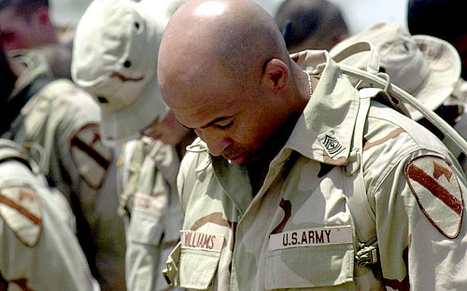 1st Sgt. Ferrell Williams, of Company C, bows his head after the reading of the traditional silent roll call when the company first sergeant called the names Spc. Ervin Caradine Jr. and Pvt. Jeremy L. Drexler three times — with no reply.