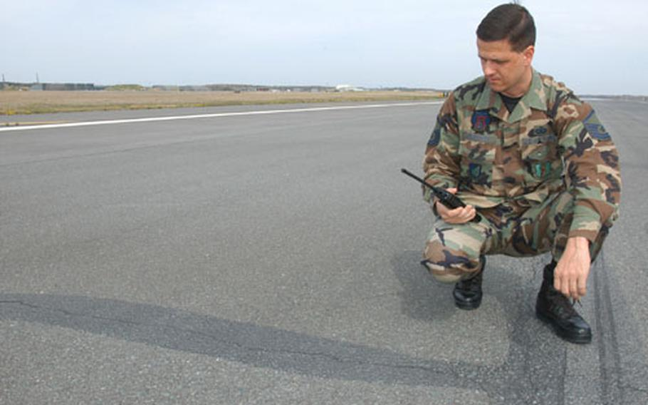 Master Sgt. Johnny Duraccio, chief of airfield management for the 35th Operations Support Squadron at Misawa Air Base, Japan, checks on an extensive surface crack in the base's asphalt runway. The airstrip will close June 4 through June 17 for major repairs.