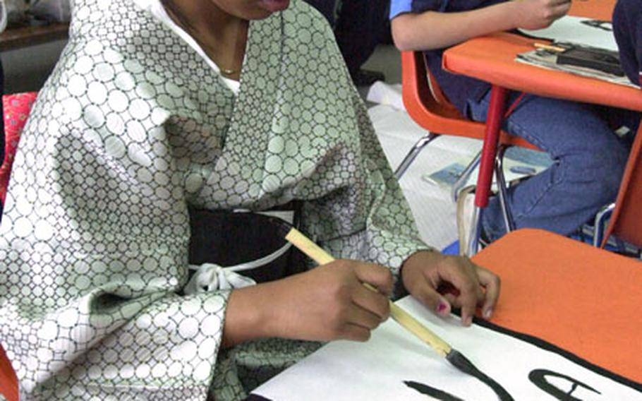 Fourth grader Asia Jackson tries writing an old Chinese character during a Shodo calligraphy exhibition during the Nihon Matsuri festival at Yokota West Elementary School on Wednesday.