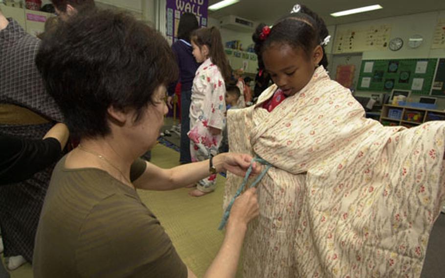 Kindergartener, Dominique Goden gets prepped for her obi to be tied on her kimono from Hiroko Kuga during the Nihon Matsuri festival held at Yokota West Elementary School Wednesday.
