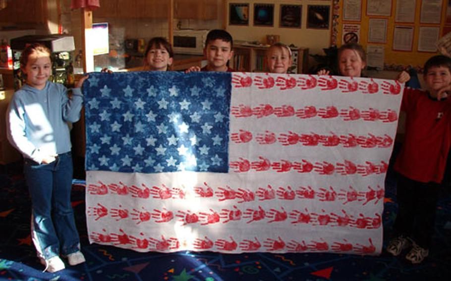 Children in the School Age Program at RAF Mildenhall Youth Center, England, show off the flag they made for troops in Iraq.