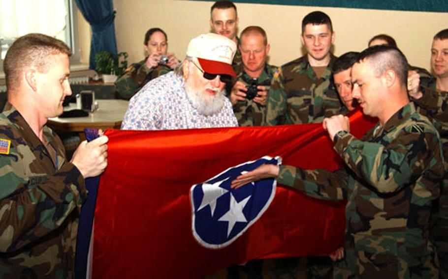 Charlie Daniels signs a Tennessee state flag while members of the Tennessee National Guard look on Thursday at the Wiesbaden Army Airfield Fining Facility. The 2nd Battalion, 115th Field Artillery soldiers are filling in as provisional military police in Stuttgart, Heidelberg, Mannheim and Kaiserslautern, Germany.