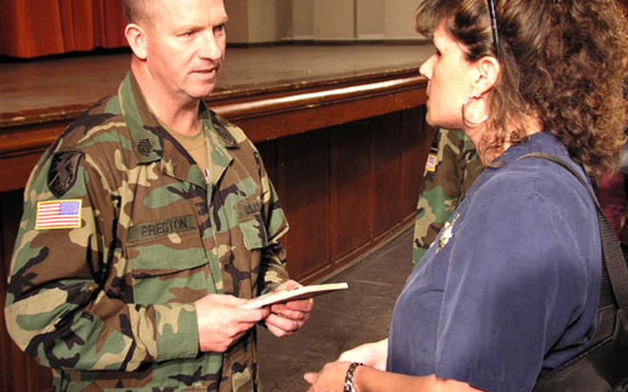 Sergeant Major of the Army Kenneth O. Preston talks with Family Readiness Group Co-Leader Shelby Barrett during his visit with family members from V Corps' 1st Armored Division at the Wiesbaden Army Airfield, Germany, May 4.